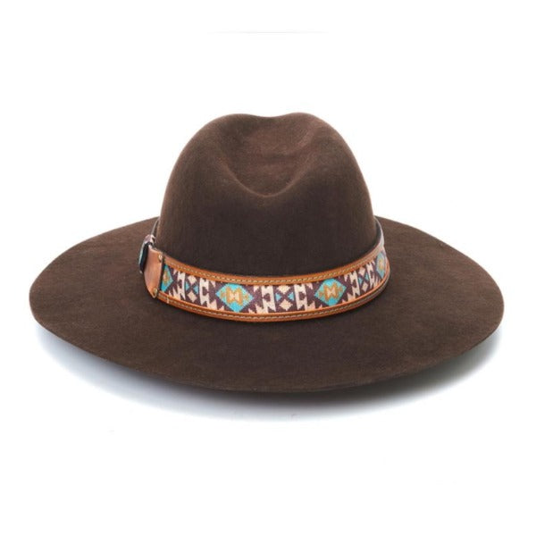 Brown flat brim rancher hat from Stamepde brand with a fedora crown. The aztec rpint fabric and leather band has purple, brown, and teal colors.