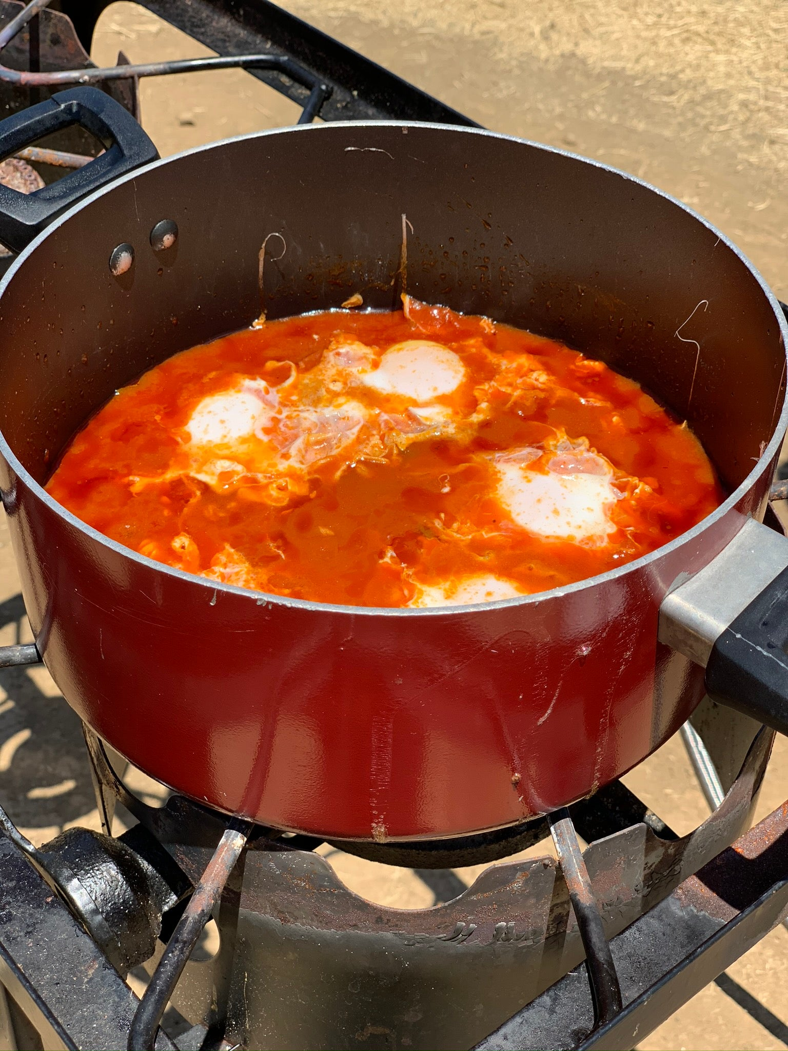 Shakshuka cooking on a stove in a cast iron pan