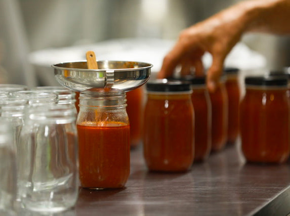 Production in the kitchen, jars being filled and sealed