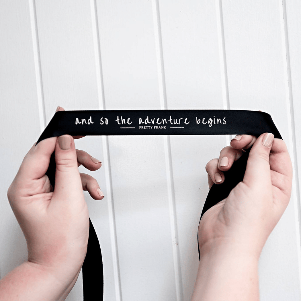 "Black ""And so the adventure begins"" ribbon"