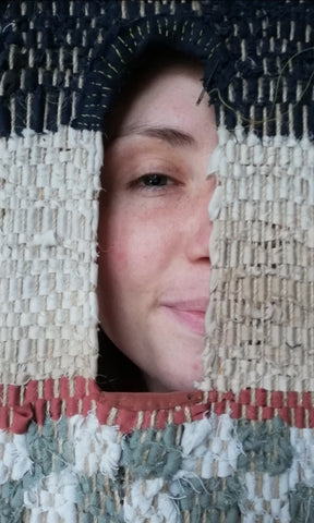 Shot of Emily Unsworth White looking through her woven shrine window