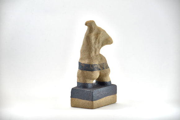 Title: Plinth Woman Artist: Sally Fitchard Medium: clay sculpture Size: 21.5 cm x 11 cm x 7.2 cm (back view, left side). Colour comprises sand and charcoal
