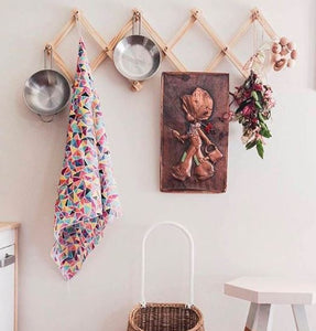 accordian rack hanging in a child room against a pale pink wall. dried flowers, pots and a picture hang from the peg hooks.