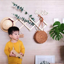 Load image into Gallery viewer, A dark haired boy standing int from of a grasspaper wall. An accordian rack hangs above with a straw hat and woven bag. He wears a yellow tee shirt.