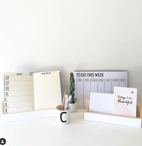 A group of stationery items sitting on a white table. Shown are a diary, a wall planner and a pencil cup and a mail holder in white.