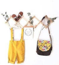 Load image into Gallery viewer, accordian hanging rack displays a childs handbag, dried leaves,  yellow overalls and brown shoes on a white wall.