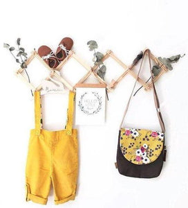 accordian hanging rack displays a childs handbag, dried leaves,  yellow overalls and brown shoes on a white wall.