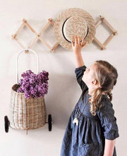 Load image into Gallery viewer, A girl places her straw hat on the accordian hanging rack. She wears pigtails and a navy blue dress with sleeves. A cane basket holding purple flowers hangs next to her. The wall is pale cream.