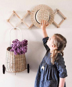 A girl places her straw hat on the accordian hanging rack. She wears pigtails and a navy blue dress with sleeves. A cane basket holding purple flowers hangs next to her. The wall is pale cream.