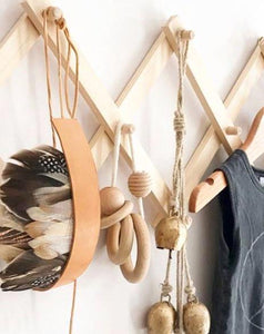 A close up of a timber accordian hanging rack on a white wall.  Displays a feather headdress, trinkets and a child's outfit.