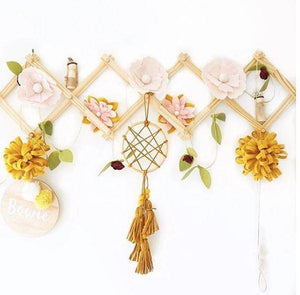 accordian hanging rack displays pink felt flowers, a mustard dream catcher and two mustard pom poms against a white wall.