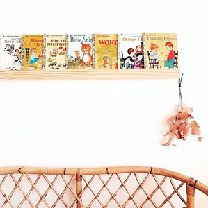 timber book ledge filled with children's books on a white wall sitting over a cane lounge chair