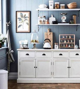 A deep blue kitchen with white cabinetry and shelving. displayed are kitchen wares along with a pantry rack sitting on the counter top. This image is from Home Beautiful Magazine .