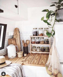 A renovated caravan kitchen with bright white walls and a timber benchtop. A patry rack sits on the bench along with a white kettle, chopping boards and kitchen utensils.