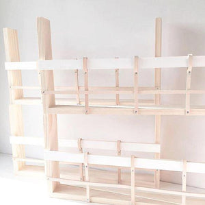 Four timber and leather book racks stacked on top of each other. They are empty to show the structure of the design and they are white in colour.