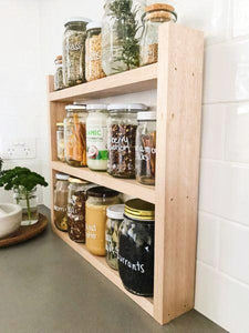 A side view of pantry jars sitting in the timber pantry rack. The shelf sits on a grey stone bench with white subway tiles behind.