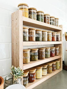 Little Label Co Pantry jars with labels sitting in the timber pantry rack. The shelf sits on a grey stone bench with white subway tiles behind.