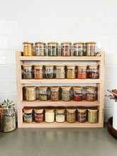 Load image into Gallery viewer, The timber spice rack sits on a grey stone bench with white subway tiles behind. The spice rack is filled with Little Label Co jars and labels.