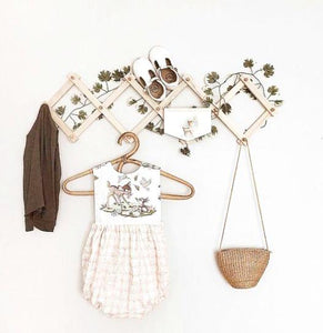 accordian hanging rack displays a childs handbag, dried flowers and a white child's dress, white shoes and brown cardigan on a white wall.