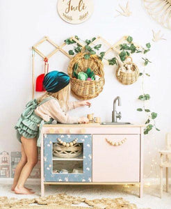 a small girl playing with a pink timber play kitchen. A timber accordian hanging rack displays cane baskets and green trailing plants on the wall above. The girl wears a peacock green velvet hat.