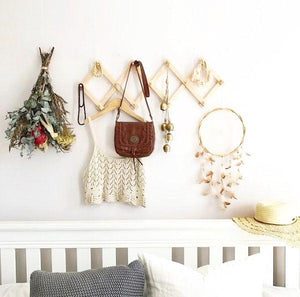 accordian hanging rack displays trinkets, dried flowers, a crochet top, brown leather bag and feather dream catcher above a white timber double bed. The wall behind is white.