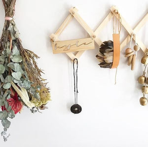 A close up of a timber accordian hanging rack on a white wall.  Displays a feather headdress, trinkets and a dried flower arrangement hangs on the wall next to it.
