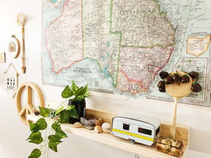 A child's bedroom wall displays a large map of Australia. Underneath sits a simple pine shelfie with various toys and ornaments displayed.