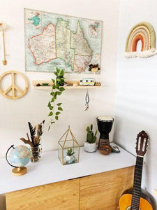 A cabinet in the corner of a child's room with ornaments and toys displayed. A simple pine shelfie sits on the wall above, along with a map of Australia and other decor items.