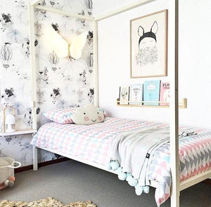 a beautiful girls room with a four poster bed and lovely wallpaper with  pale pinks and greys.