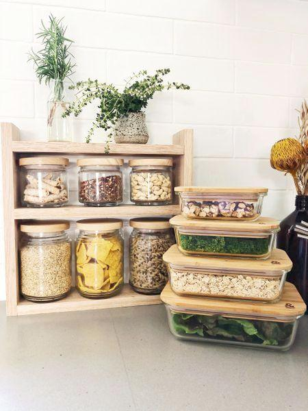 Seed and srout Co Pantry jars sitting in the timber pantry rack. The shelf sits on a grey stone bench with white subway tiles behind. A stack of 4 food storage boxes sit to the right.