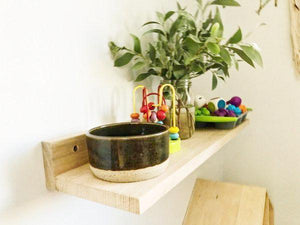 close up of trio of shelves holding pots, toys and sensory play objects.