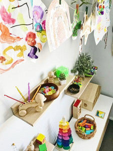 A colourful scene of trio of shelves holding wooden toys and colourful sensory play objects.