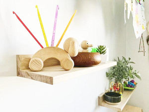 close up of trio of shelves holding wooden toys and sensory play objects.