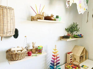 A child's bedroom wall a trio of shelves holding wooden toys, baskets and colourful objects.