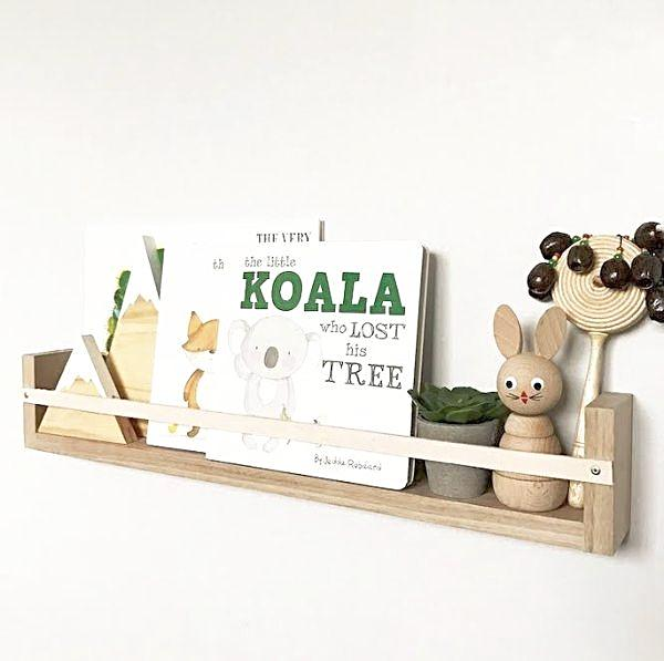A Tasmanian Oak natural leather book rack, on a white wall, filled with children's books and small toys.