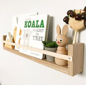 A detailed shot Tasmanian Oak natural leather book rack, on a white wall, filled with children's books and small toys.