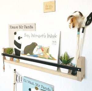 A Tasmanian Oak black leather book rack, on a white wall, filled with children's books and small toys.