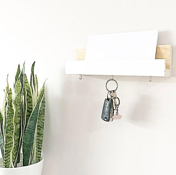 a  key and mail holder displayed on a wall with a white envelope and a set of keys against a white wall. A green plant in a white pot sits to the left.