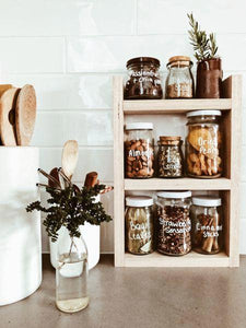 Pantry jars sitting in the timber pantry rack. The shelf sits on a brown bench with white subway tiles behind.