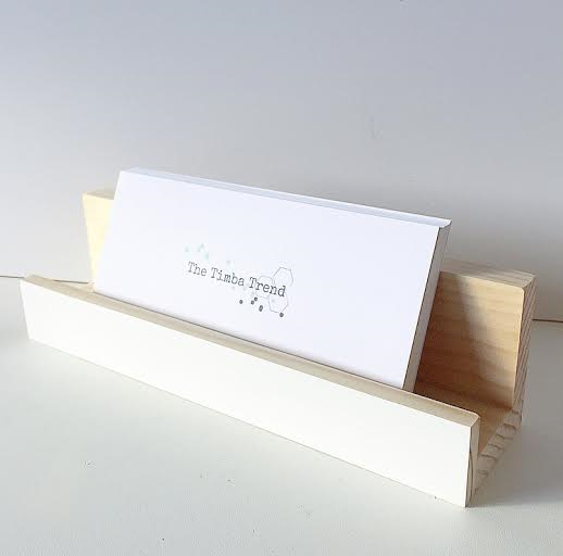 A mail holder in white displays a stack of timba trend and folk envelopes. The background is pale grey.