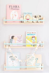 three book shelves on a pale grey wall display pastel coloured books.