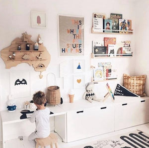 a boy sits in his room playing at a white table. The walls contain colourful art and timber bookshelves filled with colourful books. A very nice room.