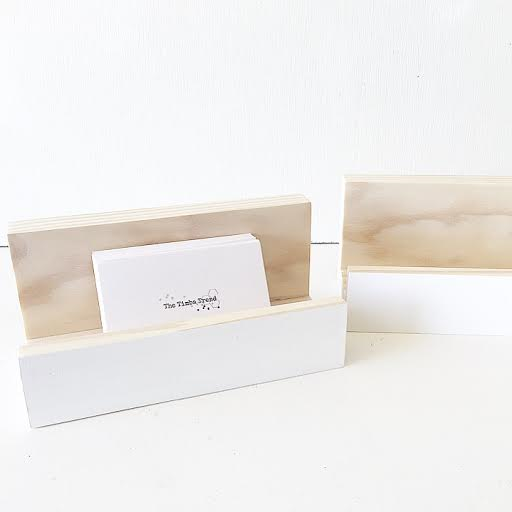 A cardholder in white displays a stack of timba trend and folk business cards. An empty card holder sits next to it.