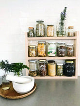 Load image into Gallery viewer, Pantry jars sitting in the timber pantry rack. The shelf sits on a grey stone bench with white subway tiles behind. A white mortar and pestle sits to the left.