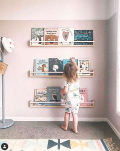 a small child reaches for books on her book shelves. The room is pale pink with grey carpet.