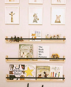 a pale pink wall with three black shelves displaying books and figurines. Framed prints of zoo animals hang above.
