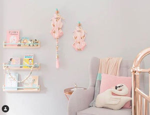 a pale grey nursery with a gold coloured crib, book shelves and a pale grey nursing chair.
