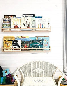 two timber bookshelves hang above a white vintage cane chair. The shelves are filled with childrens books.