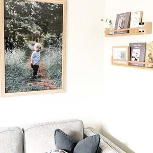 A corner of a living room with a grey sofa and two Tasmanian Oak natural leather book racks, holding framed photos and ornaments, hangs above. A large portrait of a child hangs on the adjacent wall.