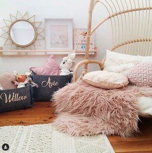 a little gilrs room with a cane chair, pink cuhsions and toys. A timber wllshelf holds framed pictures and a cane mirror shaped like the sun.